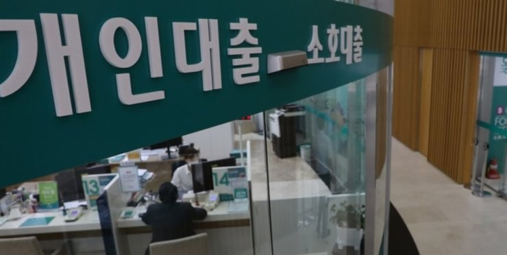 A customer speaks with a bank clerk at a Hana Bank loan sales office in Seoul in this file photo. /Yonhap
