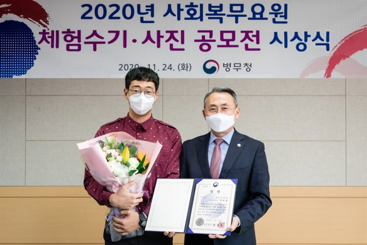 Park Se-ho, left, who has been serving at a local kindergarten helping children with disabilities for his alternative military service, poses with Military Manpower Administration Commissioner Mo Jong-hwa at the Government Complex Daejeon, Tuesday, after receiving an award for his essay about his service for the conscription agency's annual essay contest. Courtesy of Military Manpower Administration