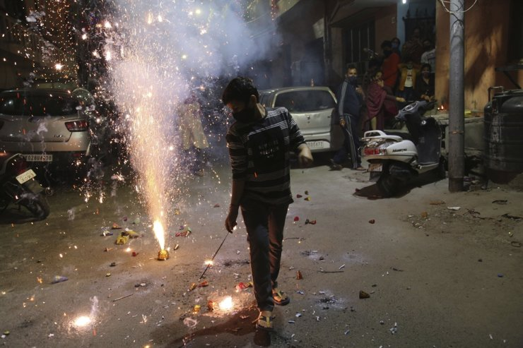 A boy plays with fireworks during Diwali, the Hindu festival of lights, in Jammu, India, Saturday, Nov. 14, 2020. AP