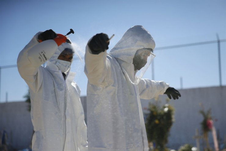 Gravediggers spray each other down with a water and bleach mixture after burying someone who has died of COVID-19, Wednesday, Nov. 11, 2020, in Ciudad Juarez, Mexico. AP