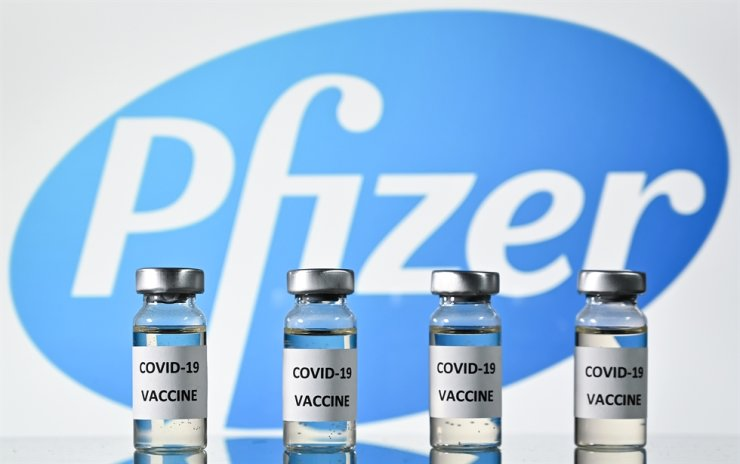Labelled vials of COVID-19 vaccine, with the logo of U.S. pharmaceutical company Pfizer in the background, are seen in this Nov. 17 file photo. AFP