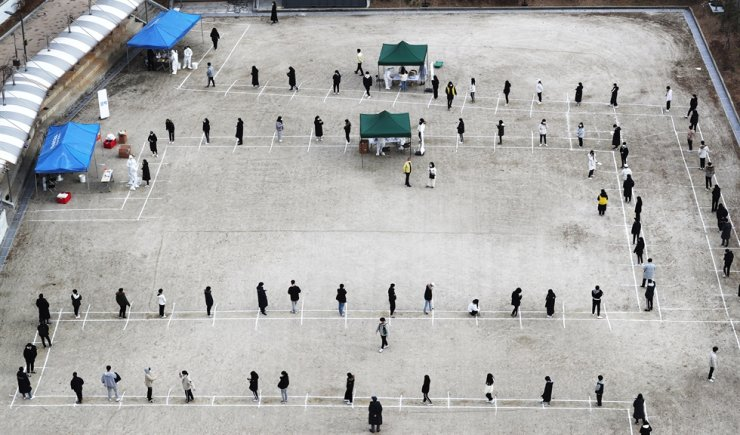 Students and teachers at a high school in Sejong City wait in line to go through COVID-19 testing, Friday, as several infections were reported there.