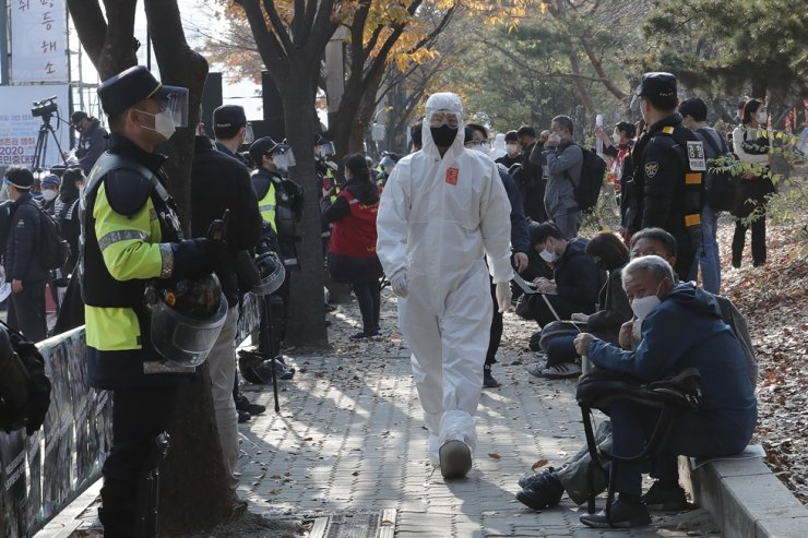 A police officer wearing a protective suit patrols as workers hold a rally to demand better working conditions in Seoul, Saturday, Nov. 14, 2020. AP