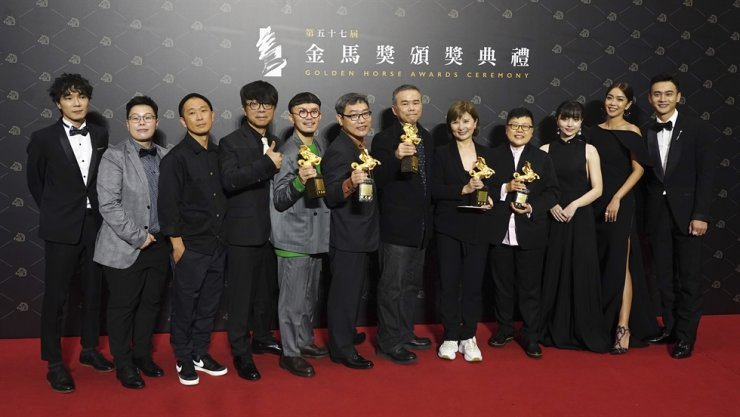 Team members of movie 'My Missing Valentine' hold their awards for press at the 57th Golden Horse Awards in Taipei, Taiwan, Saturday, Nov. 21, 2020. AP