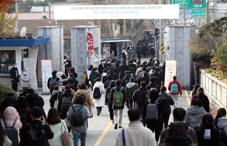 People who sat a preliminary round of test for the national teacher certification examination for 2021 at Seoul Yongsan High School in Yongsan District leave the school on Nov. 21. Yonhap