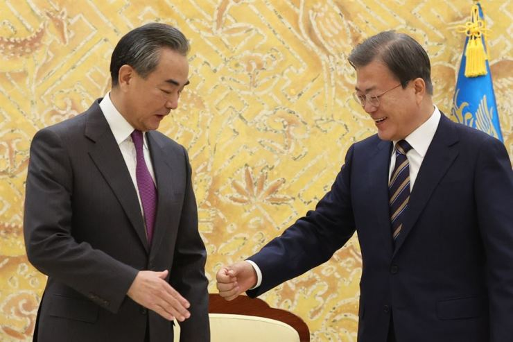President Moon Jae-in, right, greets Chinese State Councilor and Foreign Minister Wang Yi during a meeting at Cheong Wa Dae, Thursday. Yonhap