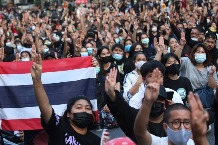 Pro-democracy protesters flash the three finger salute during a protest calling for political and monarchy reform at Ratchaprasong shopping district in Bangkok, Nov. 18, 2020. EPA