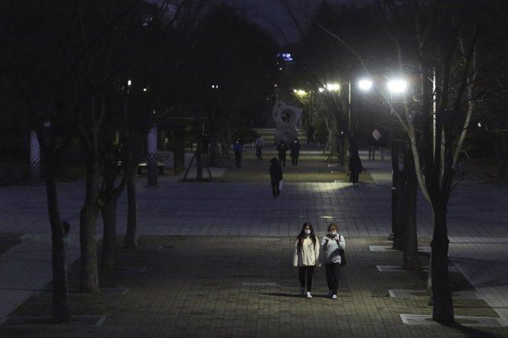 People wearing face masks walk on a street in Goyang, Korea, Sunday, Nov. 22, 2020. AP