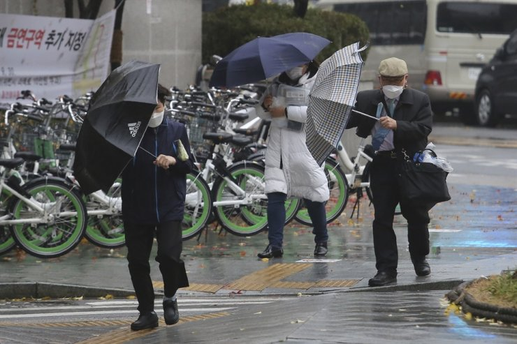 People wearing face masks try to manage their umbrellas in the rain in Seoul, Thursday, Nov. 19, 2020. AP