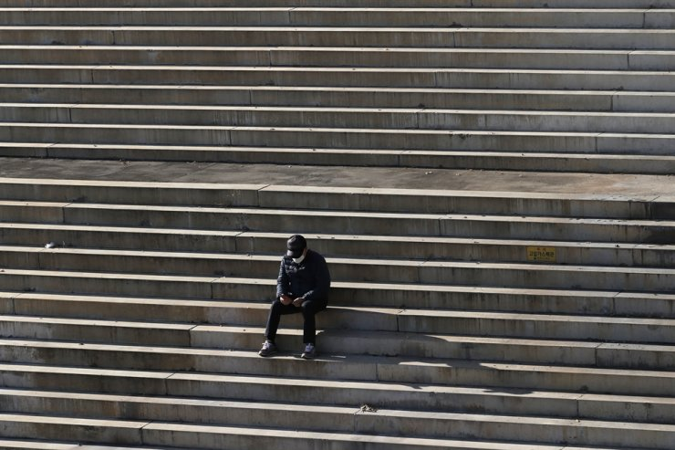 A man wearing a face mask to help curb the spread of the coronavirus sits on a set of stairs in Seoul, Monday, Nov. 23, 2020. AP