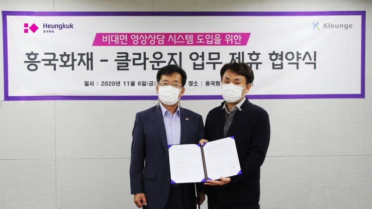 Heungkuk Fire & Marine Insurance's Managing Director Jung Woo-hyeung, left, holds a memorandum of understanding with Klounge CEO Lee Tae-ho at the headquarters of Heungkuk Fire in central Seoul, Friday. Through joint cooperation, a customer of the insurance company can have real-time consultation with claim agents about any vehicle accidents. / Courtesy of Heungkuk Fire & Marine Insurance