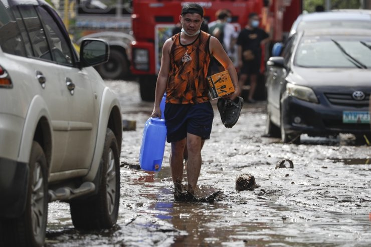 A resident walks along a mud-covered road after floodwaters caused by Typhoon Goni rose inside their village in Batangas city, Batangas province, south of Manila, Nov. 2, 2020. AP