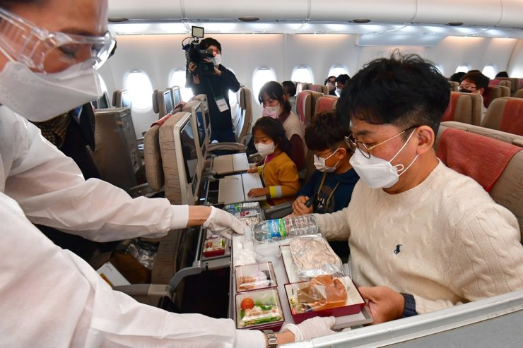An Asiana Airlines flight attendant serves in-flight meals to passengers during a flight in this October file photo. / Joint press corps.