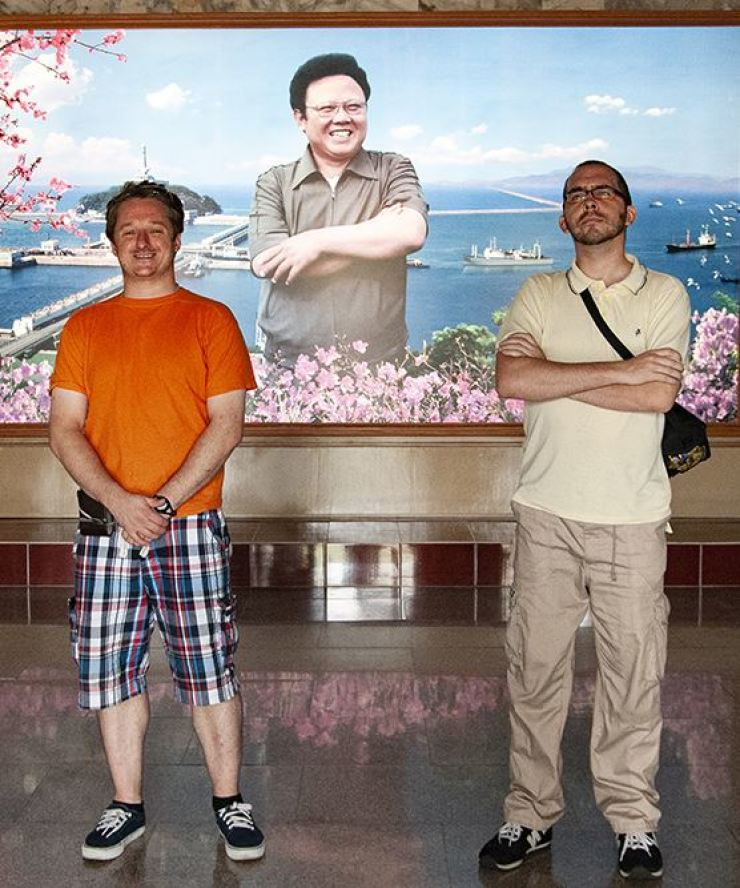 Michael Spavor, left, and now-Korea Times copy editor Jon Dunbar pose with an image of Kim Jong-il, father of North Korea's current leader, at Nampo Barrage on the west coast, in August 2010. / Courtesy of Michael's friend