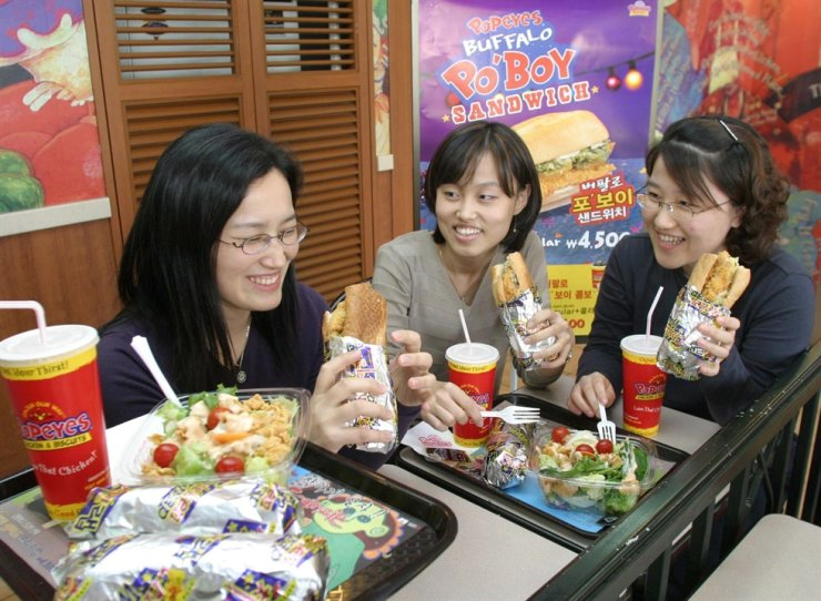 Customers eat sandwiches at a Popeyes restaurant in Seoul in this 2013 file photo. / Korea times file