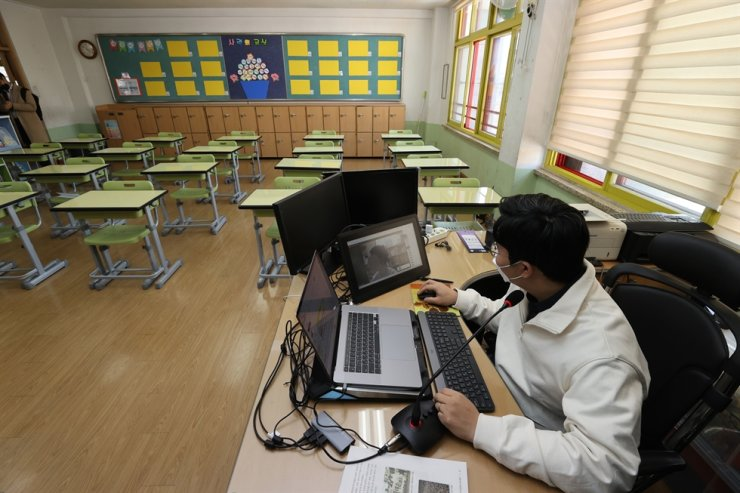 A sixth grade homeroom teacher at an elementary school in Songpa District, eastern Seoul, gives a remote lesson in this March 30 photo. / Korea Times File