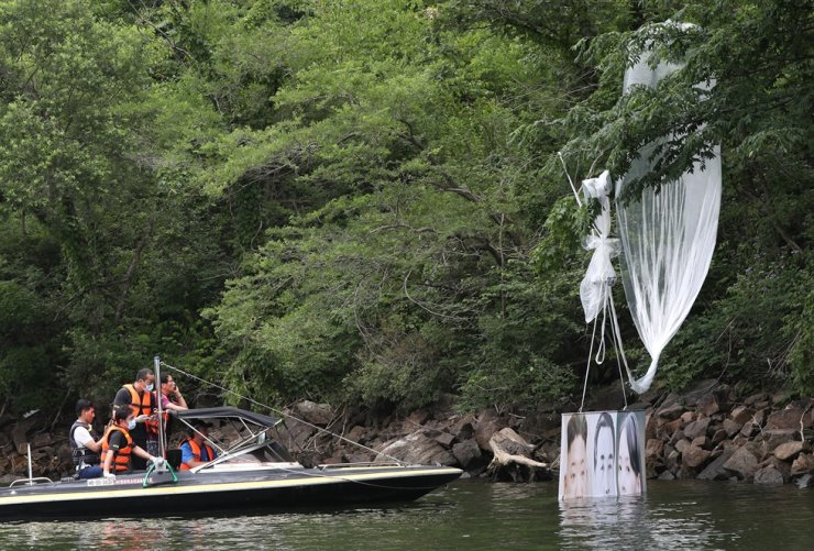 Police officers attempt to retrieve a balloon bearing an anti-North Korea banner from a mountain river in Hongcheon, Gangwon Province, June 23, as the balloon fell there after being launched a day before in the border town of Paju by a Seoul-based organization of North Korean defectors. / Yonhap
