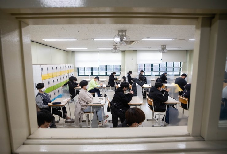 Test takers wait for the national college entrance exam to start at Yongsan High School in Seoul, Thursday. Yonhap