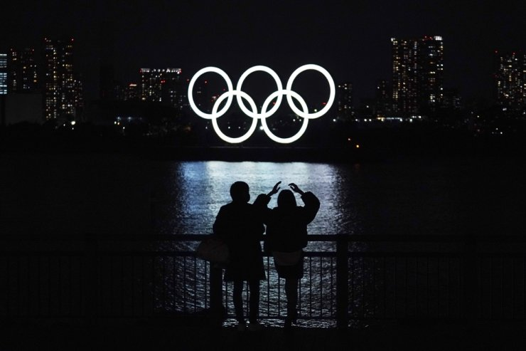 A man and a woman look at the Olympic rings float in the water in the Odaiba section in Tokyo, Tuesday, Dec. 1, 2020. AP