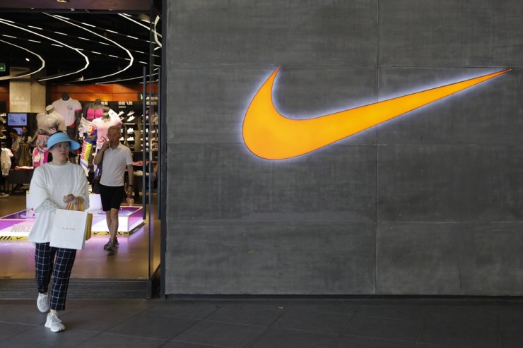 In this May 22, 2019, file photo, a woman walks past a logo of Nike outside Nike store in Beijing. A video ad from Nike Japan against bullying and racism that features biracial athletes and other minorities, such as those of Korean descent, has prompted a sharp online response including calls to boycott the company. EPA