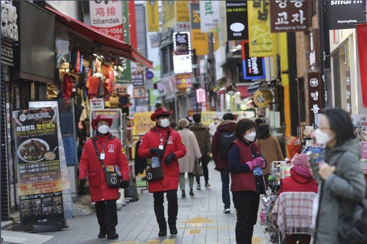 Tourist information helpers wearing face masks walk along a popular shopping street in Seoul, Wednesday, Dec. 2, 2020. AP