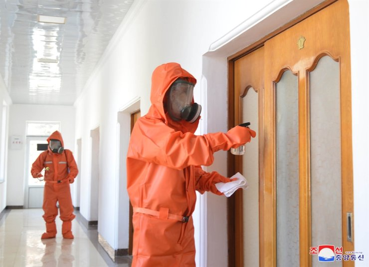 Health workers disinfect a public building in North Korea's northeastern city of Tanchon in South Hamgyong Province, Dec. 5. Yonhap