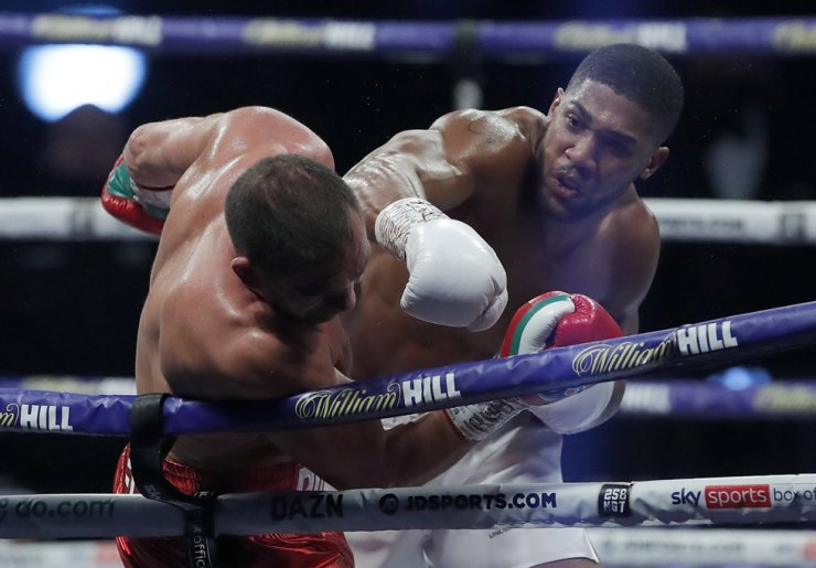 World Heavyweight boxing champion Britain's Anthony Joshua lands a blow on challenger Bulgaria's Kubrat Pulev during their Heavyweight title fight at Wembley Arena in London Saturday, Dec. 12, 2020. AP