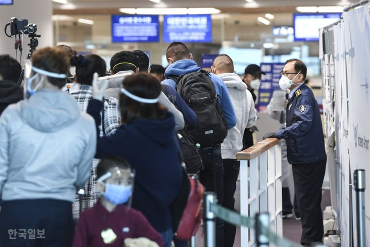 Passengers from overseas arriving at Incheon International Airport's Terminal 2 queue before examiners screening those with possible COVID-19 symptoms in April 2020. Korea Times file
