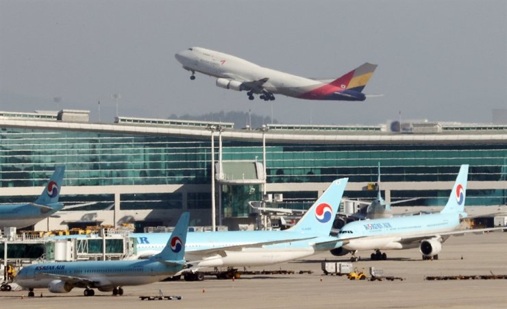 An Asiana Airlines airplane takes off the Incheon International Airport on Tuesday as Korean Air Lines airplanes remain on the ground. Yonhap