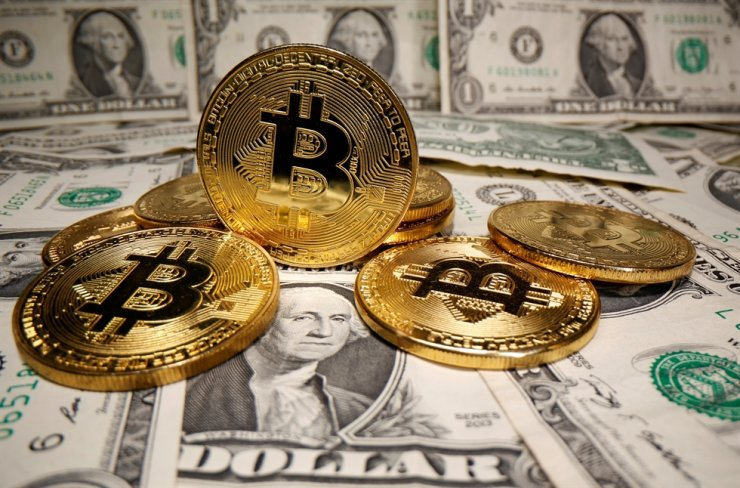 Representations of virtual currency Bitcoin are placed on U.S. Dollar banknotes in this illustration taken May 26, 2020. REUTERS-Yonhap