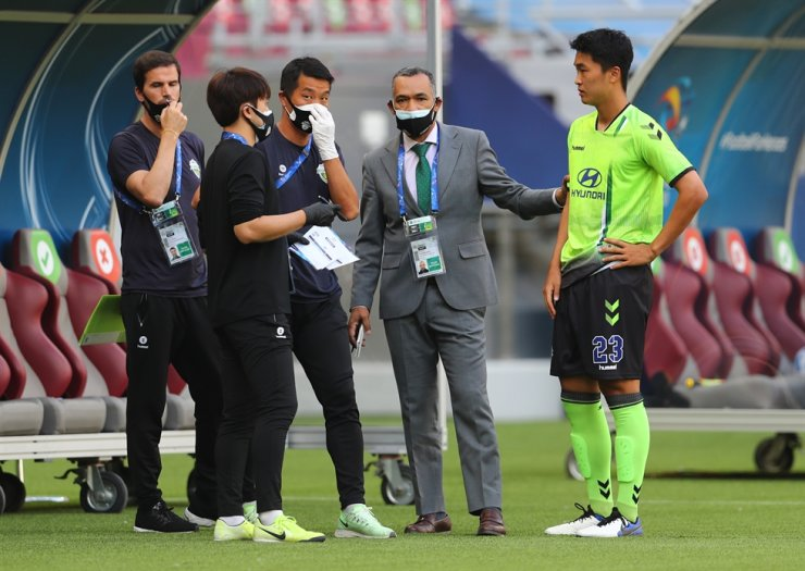 Jeonbuk Motors coach Jose Morais, second from right, speaks with Yun Ji-Hyuk, far right, before he comes on as a substitute durign the club's Asian Football Confederation Champions League Group H match against Shanghai SIPG at Khalifa International Stadium in Doha, Qatar, Dec. 4, 2020. REUTERS