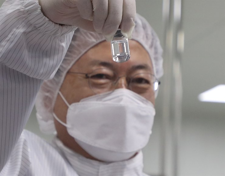 President Moon Jae-in looks at a COVID-19 vaccine during his visit to a vaccine production plant in Andong. North Gyeongsang Province, Wednesday. Yonhap