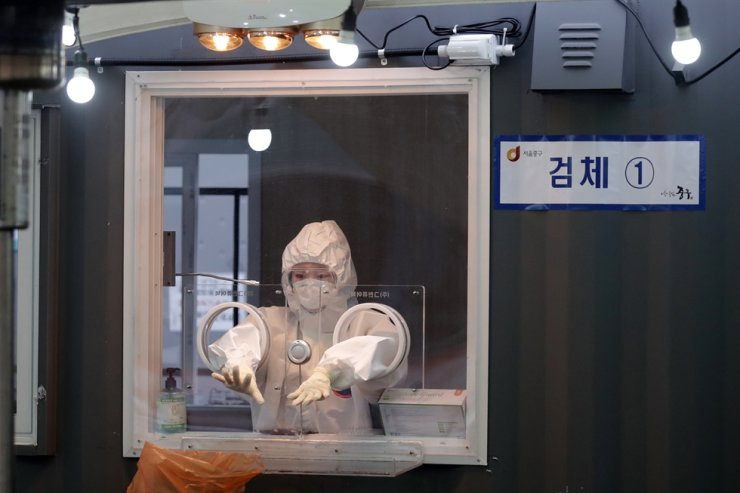 A medical worker wearing protective gear prepares to take a sample at coronavirus testing site in Seoul, Monday, Jan. 11, 2021. AP