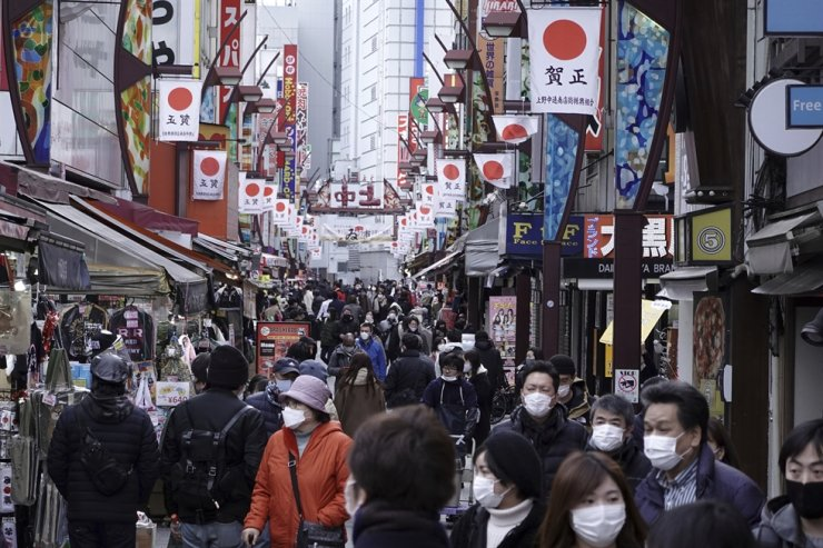 People wearing protective masks to help curb the spread of the coronavirus walk along a shopping street at Ueno area of Tokyo, Monday, Jan. 11, 2021. AP