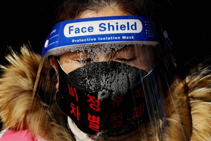 With a face shield on, a labor union member of KORAIL Networks, a subsidiary of South Korean state railway operator KORAIL, joins in the union's walkout on its 60th day at Seoul Station on Jan. 9 as they demand wage raise and improvement in working environment. Yonhap
