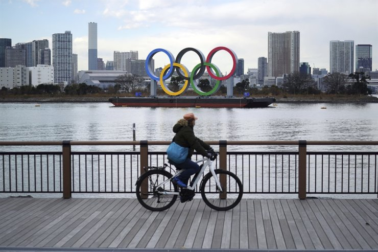 A man rides a bicycle near the Olympic rings floating in the water in the Odaiba section, Jan. 8 in Tokyo. AP-Yonhap