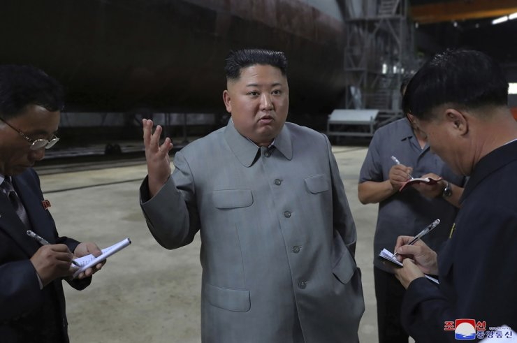 North Korea's leader Kim Jong-un, center, speaks while inspecting a newly built submarine at an unknown location in North Korea, in this undated photo provided July 23, 2019, by the country's state-run Korean Central News Agency. AP-Yonhap