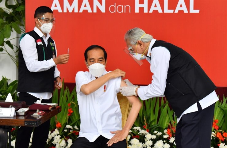 A handout photo made available by the Presidential Palace Indonesia shows Indonesian President Joko Widodo injected with a COVID 19 vaccine at the Presidential Palace in Jakarta, Jan. 13, 2021. EPA