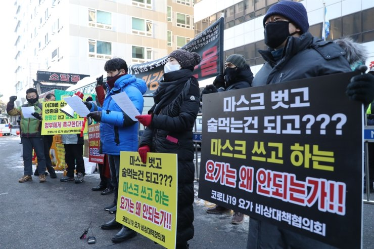 Yoga instructors gather in front of the headquarters of the ruling Democratic Party of Korea on Yeouido in the Yeongdeungpo District of Seoul, Jan. 8, demanding the central government allow them to provide lessons. The signs read, 'Drinking without putting on masks is okay but doing yoga with masks on isn't?' Yonhap
