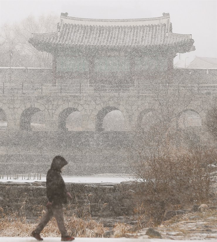 A person walks in front of Hwaseong Fortress, a UNESCO World Heritage site, in Suwon, Gyeonggi Province, Thursday, when a heavy snow advisory was issued for Seoul and northern Gyeonggi Province. Following the snowfall, the mercury dropped sharply across the country, with morning lows in the capital expected to dip to minus 12 degrees Celsius, Friday. / Yonhap