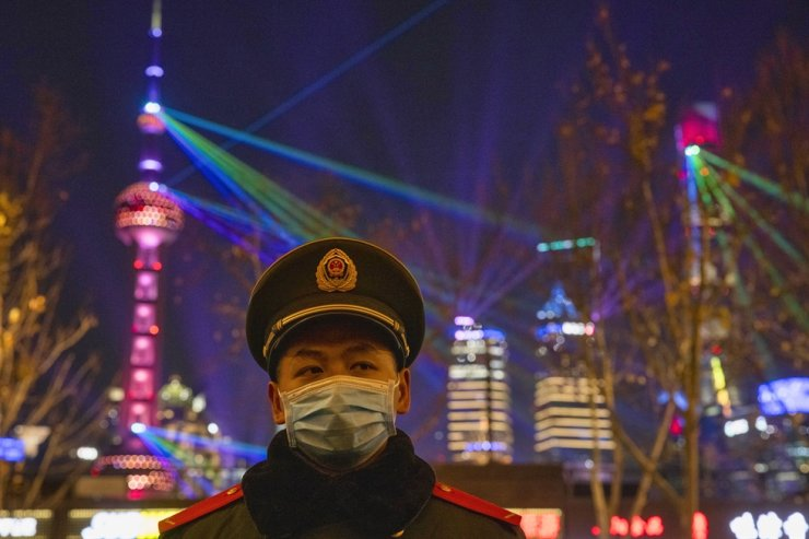 A member of the PLA guards regulates pedestrians on the Bund waterfront area during New Year's Eve celebrations in Shanghai, China, Dec. 31, 2020. EPA