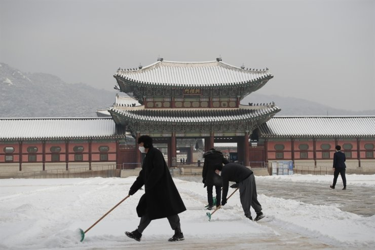 People wearing face masks as a precaution against the coronavirus clear snow at the Gyeongbok Palace in Seoul, Wednesday, Jan. 13, 2021. AP