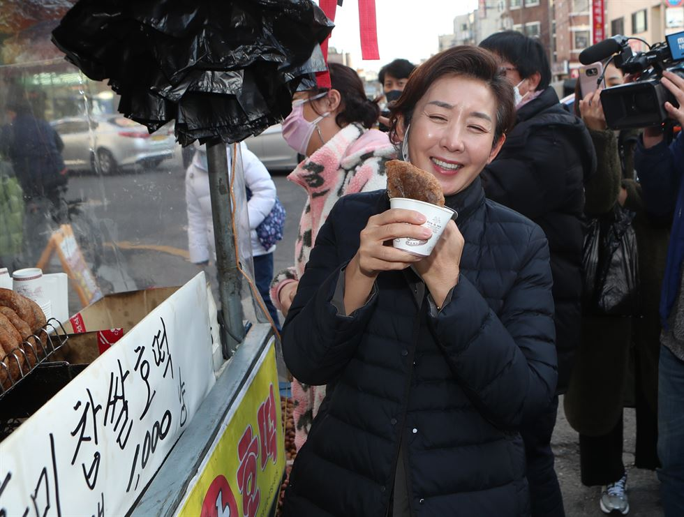 Ruling Democratic Party of Korea (DPK) Chairman Lee Nak-yon, center, eats fish cake at a stall in Namdaemun Market in central Seoul, Saturday, together with former SMEs and Startups Minister Park Young-sun, left, DPK Rep. Woo Sang-ho, right, two candidates of the DPK competing for the party's primary to run in the Seoul mayoral by-election in April. Yonhap