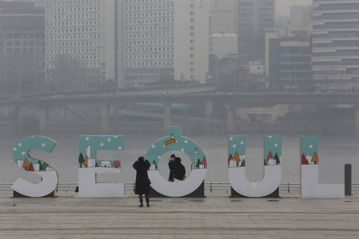 A woman wearing a face mask to help protect against the spread of the coronavirus poses for pictures at a park in Seoul, Tuesday, Jan. 26, 2021. AP