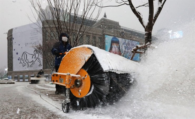 Seoul City Office employees remove snow off the roads in front of the office headquarters in Jung District on Jan. 12. Yonhap