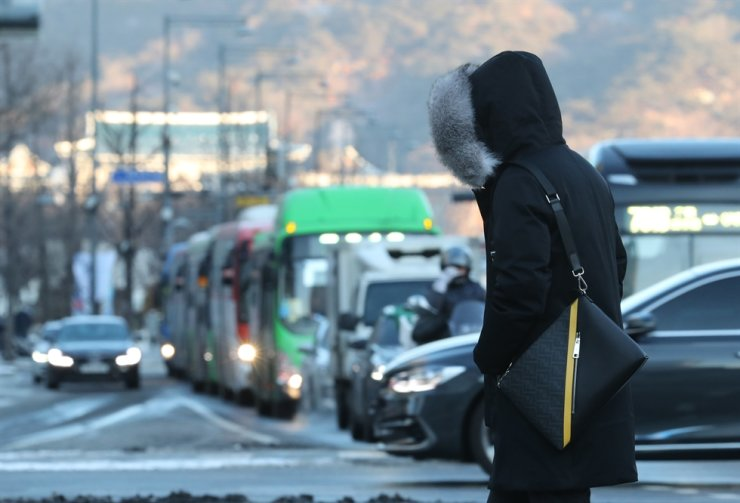 A pedestrian wearing a coat crosses the road in Seoul, Friday. The cold snap pushed temperatures down to minus 18.6 C in the capital early in the morning. Yonhap
