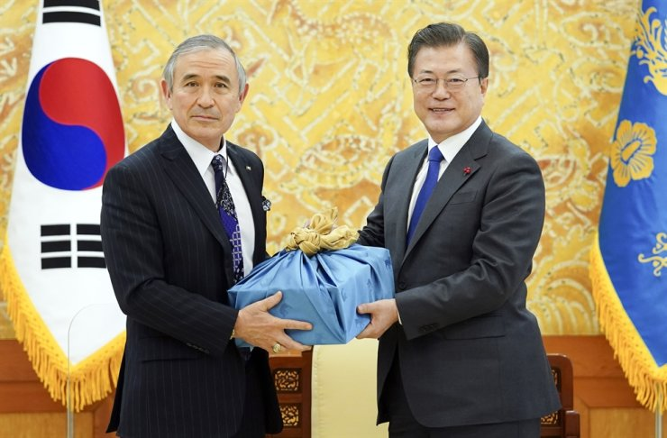 President Moon Jae-in gives outgoing U.S. Ambassador to South Korea Harry Harris a gift box containing Andong soju, a type of traditional Korean liquor produced in the Andong region in North Gyeongsang Province, during the latter's courtesy visit to Cheong Wa Dae, Tuesday. The meeting was held a day before Harris leaves office in line with the change in leadership in the U.S. During the meeting, Moon vowed to continue to keenly cooperate with the incoming Joe Biden administration to achieve peace on the Korean Peninsula. / Yonhap