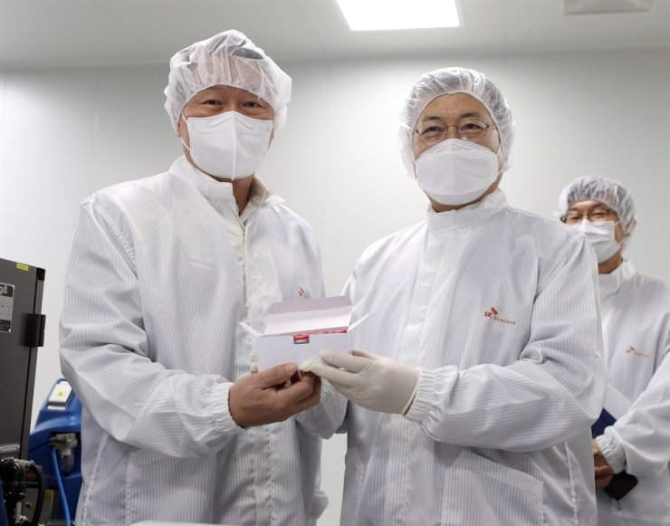 President Moon Jae-in poses with SK Group Chairman Chey Tae-won, left, during a visit to SK Bioscience's plant in Andong, North Gyeongsang Province, Wednesday. Yonhap