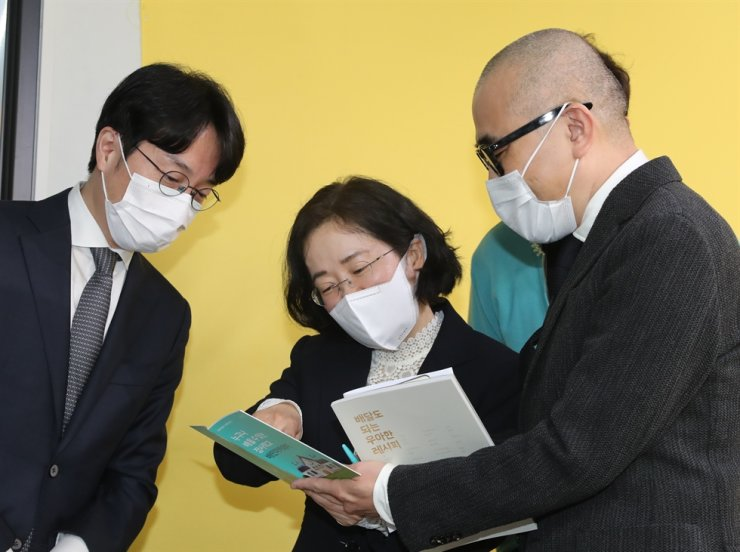 Fair Trade Commission Chairwoman Joh Sung-wook, center, listens to Woowa Brothers founder Kim Bong-jin, right, and CEO Kim Beom-joon at Baemin Academy Studio in Seoul, Friday. / Yonhap