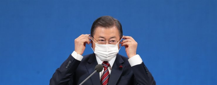 President Moon Jae-in puts on his face mask after finishing a New Year press conference held at Cheong Wa Dae, Monday. / Yonhap